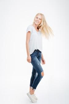 Volledig lengteportret van een glimlachende jonge vrouw die zich geïsoleerd op een witte achtergrond bevindt