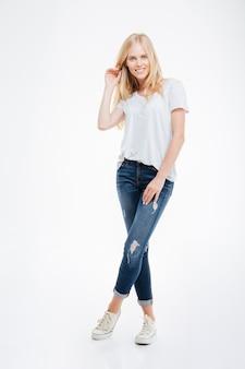 Volledig lengteportret van een glimlachende jonge vrouw die zich met gekruiste benen bevindt dat op een witte achtergrond wordt geïsoleerd