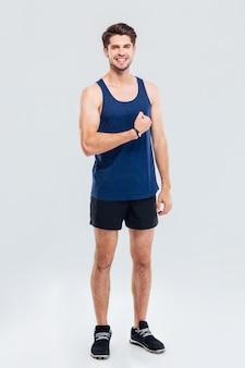 Volledig lengteportret van een glimlachende mens die zijn biceps toont die op een grijze achtergrond wordt geïsoleerd