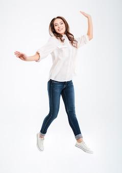 Volledig lengteportret van een glimlachende mooie vrouw die geïsoleerd op een witte muur springt