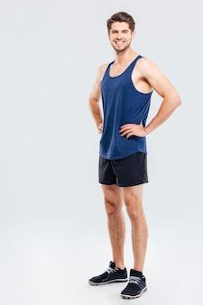 Volledig lengteportret van een glimlachende sportman die zich met handen op heupen bevindt die op een grijze achtergrond wordt geïsoleerd