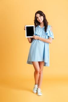 Volledig lengteportret van een glimlachende toevallige vrouw die het lege geïsoleerde scherm van de tabletcomputer toont
