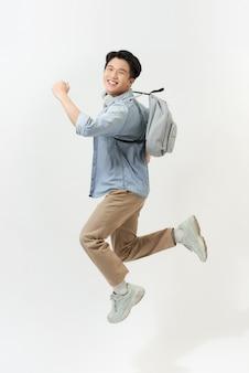 Volledig lengteportret van een grappige vrolijke mannelijke student die op witte achtergrond springt