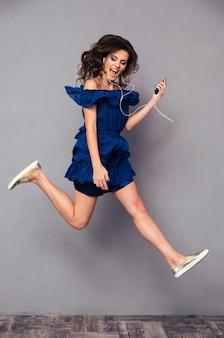 Volledig lengteportret van een grappige vrouw in jurk die muziek luistert en op grijze bakground springt