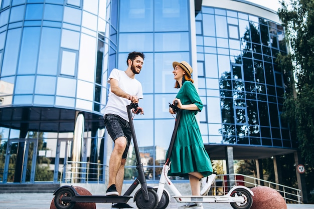 Volledig lengteportret van een jong romantisch paar met elektrische autopedden, lopend in de stad. jonge vrouw in hoed en man genieten van een wandeling