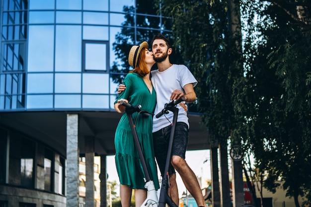 Volledig lengteportret van een jong romantisch paar met elektrische autopedden op een datum, die in de stad lopen. jonge vrouw in hoed en man geniet van een wandeling