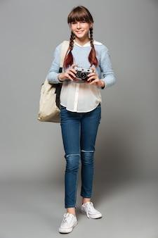 Volledig lengteportret van een jong vrolijk schoolmeisje
