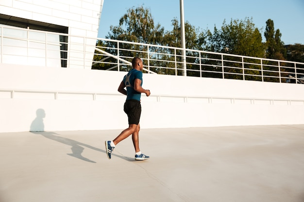 Volledig lengteportret van een jonge afrikaanse sportman in oortelefoons