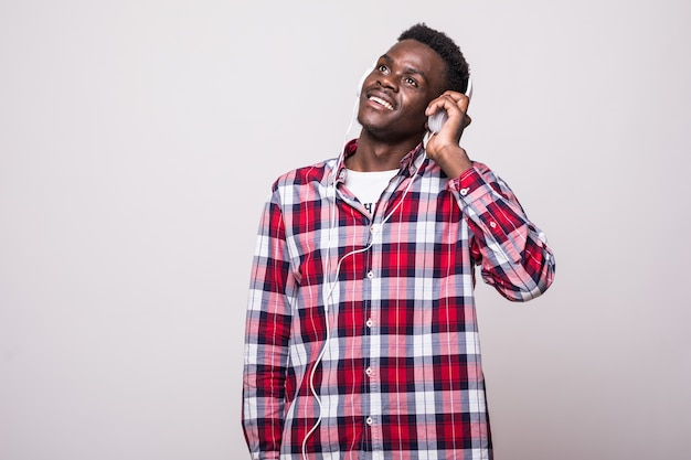 Volledig lengteportret van een jonge afro-amerikaanse mens die aan muziek met geïsoleerde hoofdtelefoons luistert