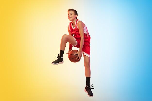 Volledig lengteportret van een jonge basketbalspeler met bal op gradiëntmuur