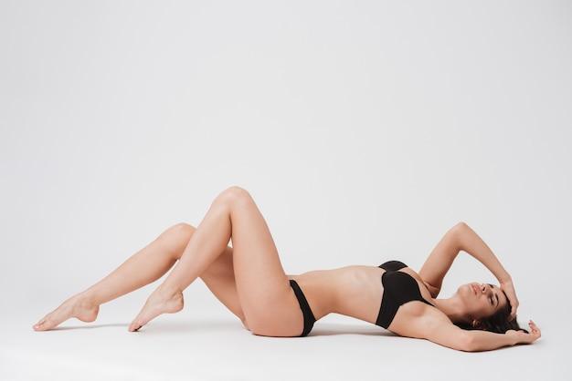 Volledig lengteportret van een jonge donkerbruine vrouw die op haar rug met gesloten ogen op wit oppervlak rust