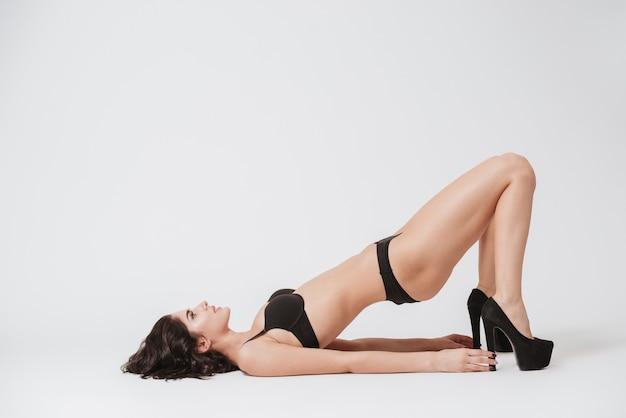 Volledig lengteportret van een jonge donkerbruine vrouw in lingerie en hoge hielenschoenen die op haar geïsoleerde rug leggen
