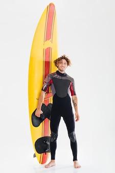 Volledig lengteportret van een jonge gelukkige surfer die surfplank houdt die op de witte achtergrond wordt geïsoleerd
