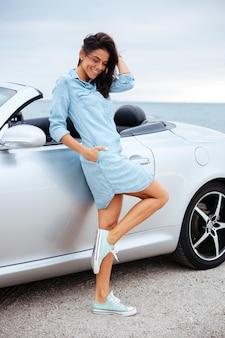Volledig lengteportret van een jonge gelukkige vrouw die zich dichtbij haar auto in openlucht bevindt
