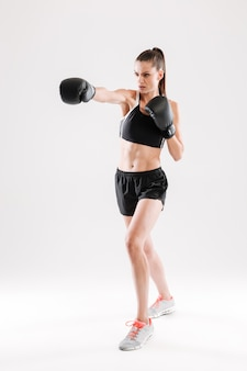 Volledig lengteportret van een jonge gemotiveerde vrouw die het in dozen doen doet