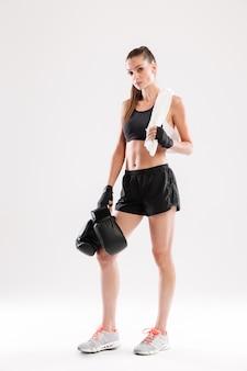 Volledig lengteportret van een jonge geschikte sportvrouw met handdoek