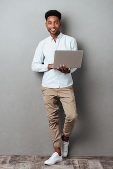 Volledig lengteportret van een jonge glimlachende afrikaanse mens