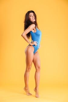 Volledig lengteportret van een jonge mooie vrouw in zwempak poseren geïsoleerd op de oranje muur