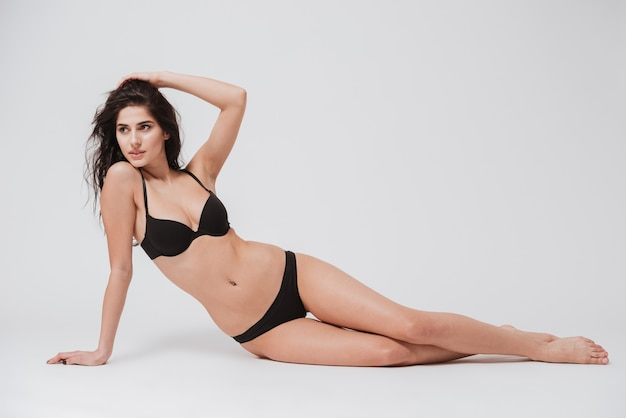 Volledig lengteportret van een jonge sexy vrouw in lingerie die op de vloer ligt die op wit wordt geïsoleerd