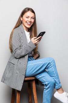 Volledig lengteportret van een jonge slimme vrouwenzitting op de stoel met mobiele telefoon