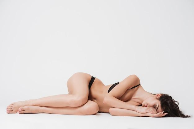 Volledig lengteportret van een jonge tedere vrouw in lingerie die op een kant ligt met gesloten ogen op een witte ondergrond