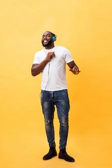 Volledig lengteportret van een kersen jonge afrikaanse amerikaanse mens die aan muziek met hoofdtelefoons luisteren