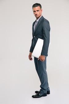 Volledig lengteportret van een knappe zakenman die zich met laptop over grijze ruimte bevindt