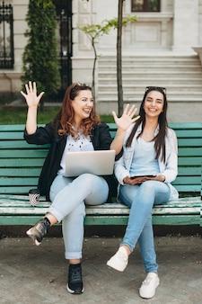 Volledig lengteportret van een lichaams positieve vrouwelijke zittend op een strand met een laptop op haar benen verhaal vertellen aan haar vriend