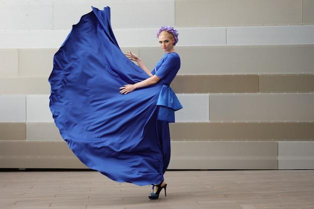Volledig lengteportret van een maniervrouw met haar kleding die in de lucht vliegt