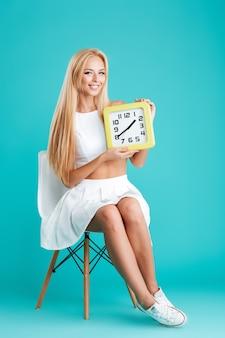 Volledig lengteportret van een mooi glimlachend meisje dat muurklok houdt en op stoel zit die op de blauwe achtergrond wordt geïsoleerd