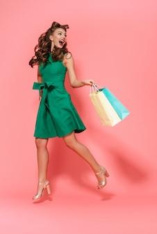 Volledig lengteportret van een mooi jong speld-omhooggaand meisje dat geïsoleerde kleding draagt, die het winkelen zakken draagt
