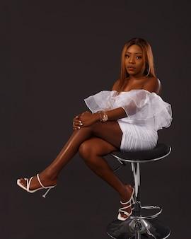 Volledig lengteportret van een mooie afrikaanse amerikaanse vrouw, kortom witte jurk zittend op een stoel op zwarte achtergrond