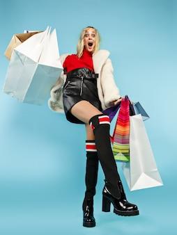 Volledig lengteportret van een mooie glimlachende vrouw die met geïsoleerde over kleurrijke het winkelen zakken loopt