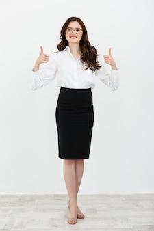 Volledig lengteportret van een mooie vrouw in een kostuum dat een geïsoleerde duim opgeeft