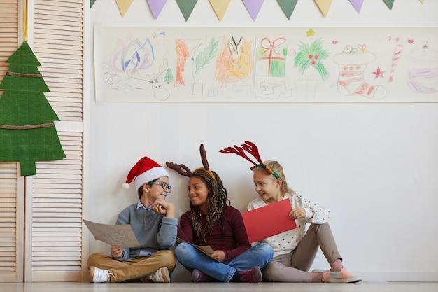 Volledig lengteportret van een multi-etnische groep kinderen die op vloer zitten die foto's houden terwijl u geniet van kunstles op kerstmis, exemplaarruimte