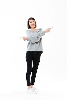 Volledig lengteportret van een opgewekte gelukkige vrouw die vingers in beide richtingen richt die over wit worden geïsoleerd