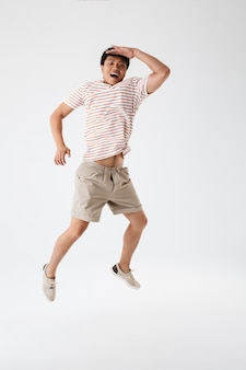 Volledig lengteportret van een opgewonden jonge aziatische mens