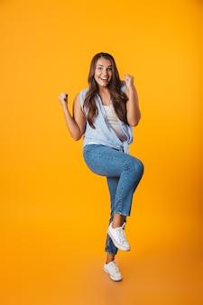 Volledig lengteportret van een opgewonden jonge toevallige vrouw, die succes viert