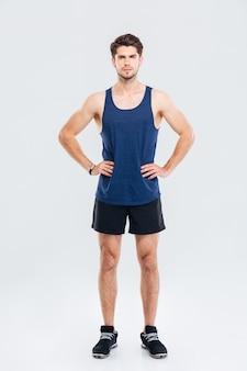 Volledig lengteportret van een serieuze sportman die met de handen op de heupen staat geïsoleerd op een grijze achtergrond