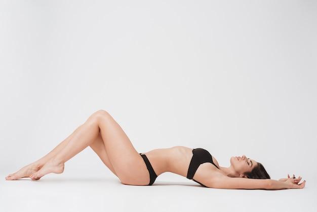 Volledig lengteportret van een sexy donkerbruine vrouw die op haar rug ligt met gesloten ogen op een witte ondergrond