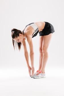 Volledig lengteportret van een slanke sportvrouw die rekoefeningen doet