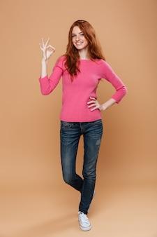 Volledig lengteportret van een vrolijk glimlachend roodharigemeisje die het ok gebaar maken