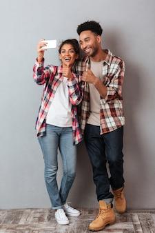 Volledig lengteportret van een vrolijk jong afrikaans paar