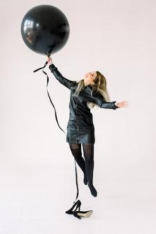 Volledig lengteportret van een vrolijk jong meisje die in zwarte kleding grote zwarte luchtballon houden terwijl springen en vliegen, bekijkend camera over witte achtergrond wordt geïsoleerd