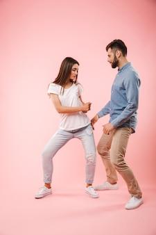 Volledig lengteportret van een vrolijk jong paar dansen