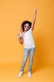 Volledig lengteportret van een vrolijk klein afrikaans meisje met amerikaanse vlag