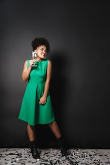 Volledig lengteportret van een vrolijke afro-amerikaanse vrouw die kleding draagt die zich over zwarte muur bevindt