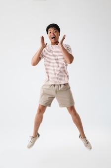 Volledig lengteportret van een vrolijke jonge aziatische mens