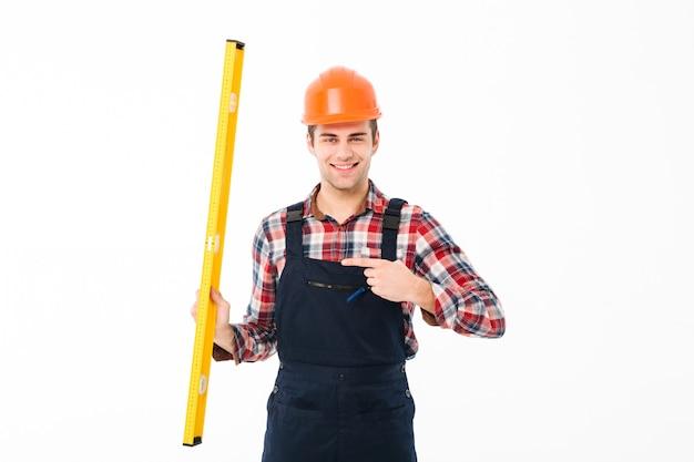 Volledig lengteportret van een vrolijke jonge mannelijke bouwer