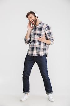 Volledig lengteportret van een vrolijke jonge mens in geruit overhemd